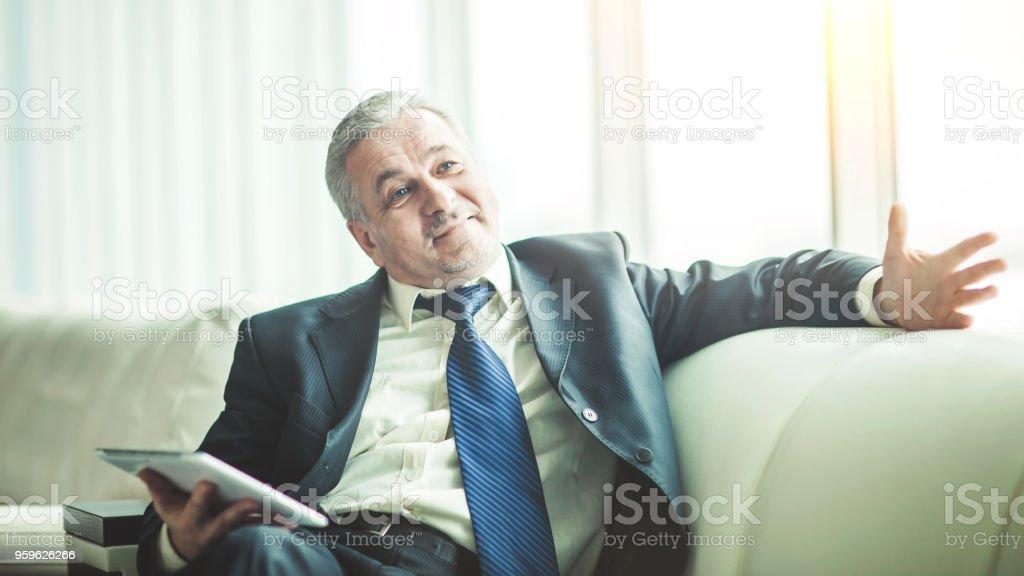 hombre de negocios acertado con tableta digital sentado en el sofá en la oficina privada - Foto de stock de Abogado libre de derechos