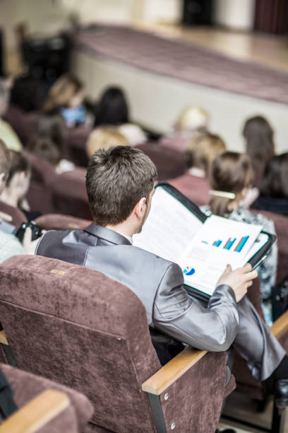 hombre de negocios acertado con documentos financieros sentados en una sala de conferencias para presentaciones de negocios - suministros escolares fotografías e imágenes de stock