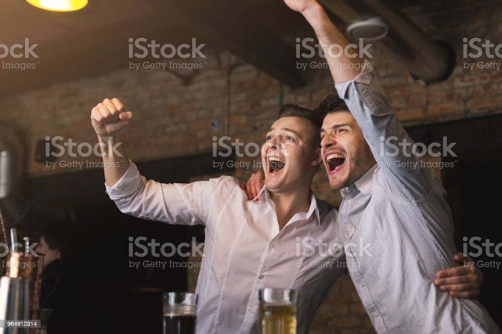 Successful businessmen drinking beer and shouting at the bar stock photo