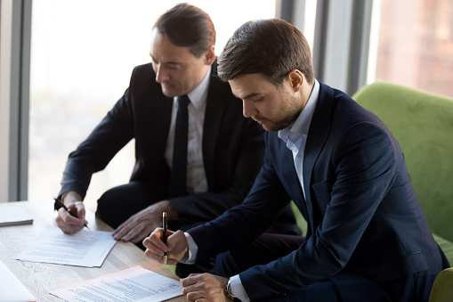 843533912 istock photo Successful businessmen in suits signing contract, partnership agreement 1265470605