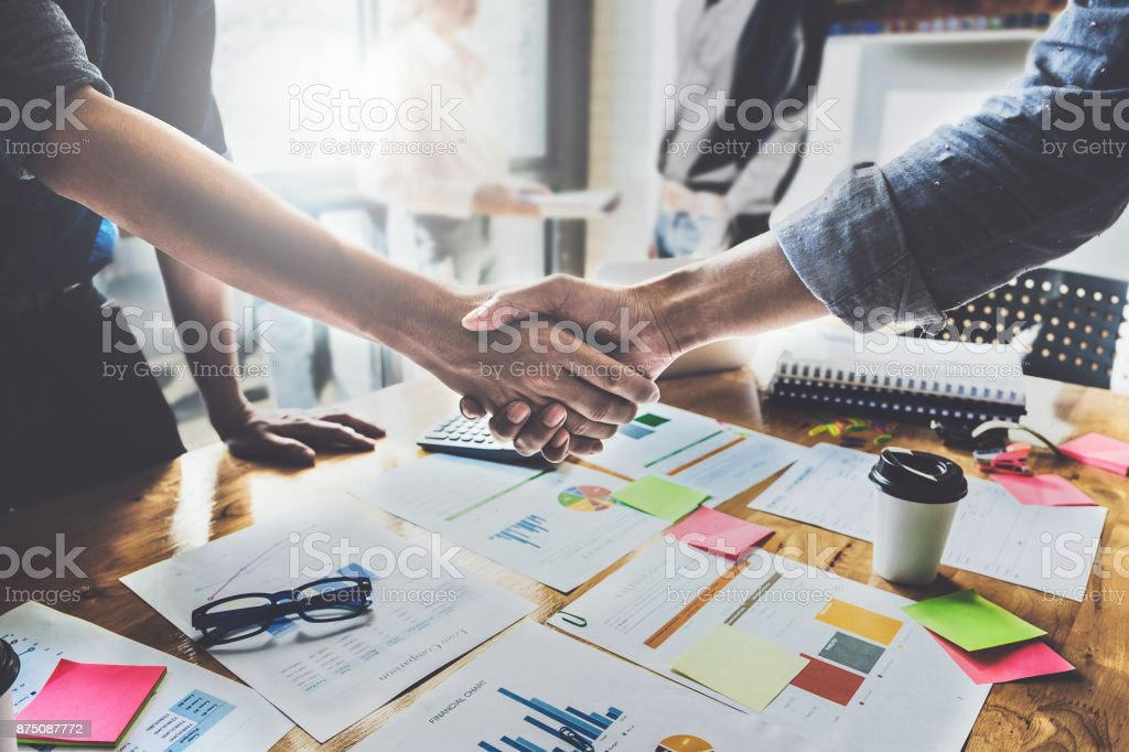 Erfolgreiche Geschäftsleute Partnerschaft Handshake nach Erwerb und berufliche Arbeit im Hintergrund. Treffen für Verträge abschliessen und Gruppe-Support-Konzept. – Foto