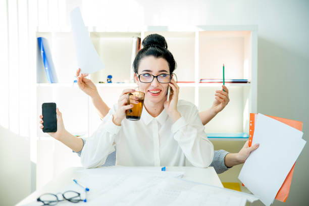 Successful businesswoman multitasking A successful businesswoman is multitasking in office multi tasking stock pictures, royalty-free photos & images