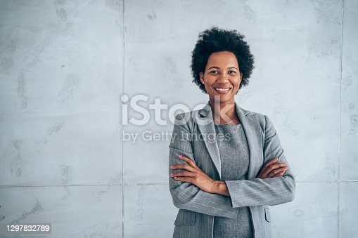 Portrait of beautiful confident smiling african-american businesswoman standing with arms crossed in the office and looking at camera.