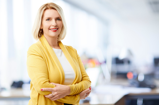 A beautiful mature sales businesswoman wearing casual clothes and smiling to you while standing with arms crossed at the office.