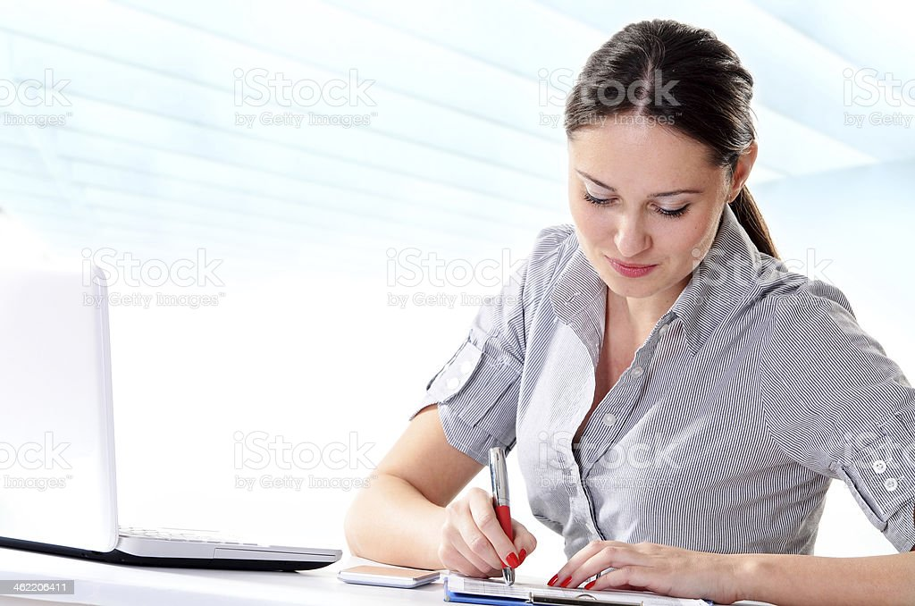 Successful businesswoman signing report, writing and smiling in modern office stock photo