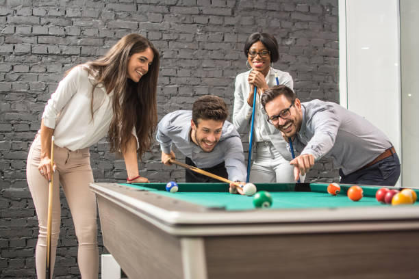 Successful cheerful business people playing snooker. stock photo