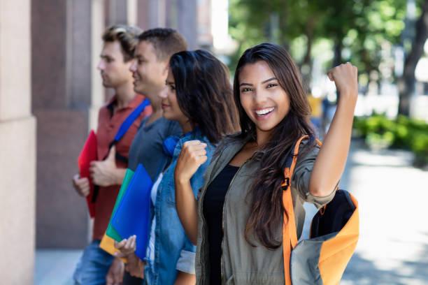 Exitosa estudiante latinoamericana con grupo de amigos - foto de stock