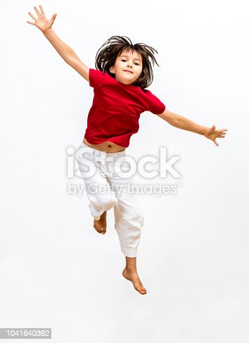 successful little child enjoying jumping and flying to express open mindedness, imagination, happiness, freedom and positive energy, isolated over white background