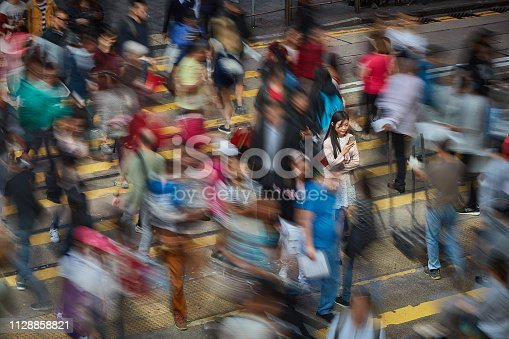 Long exposure image of Chinese businesswoman in a zebra crossing checking her mobile phone.