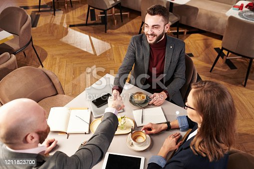 Above view of successful young businessman handshaking with representative of business company while congratulating him with deal