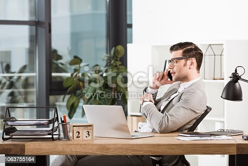 successful confident businessman talking by phone at workplace in modern office