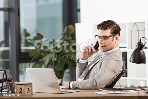 successful confident businessman talking by phone at workplace in office