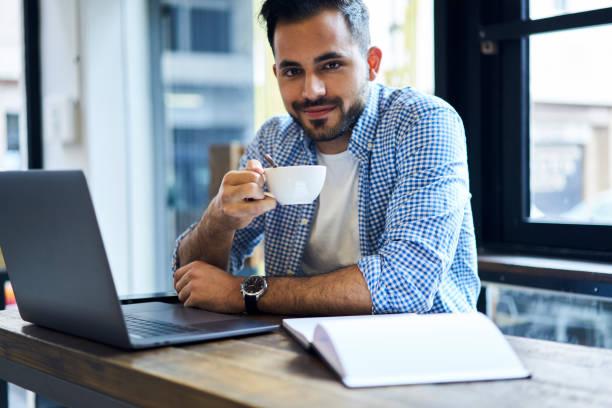 erfolgreiche zuversichtlich, ceo von arbeitstag tasse kaffee zum frühstück denken über neue software-projekt-konzept sitzen im coworking büro mit laptop-computer mit wlan-verbindung - lustige trinkspiele stock-fotos und bilder