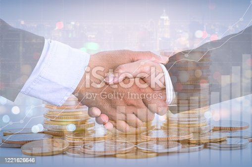 635949862 istock photo Successful cooperative, teamwork, and joint venture concept; double exposure of handshake and coins stack, with growing trend graph. 1221626646