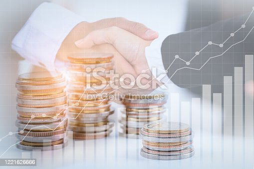 635949862 istock photo Successful cooperative, teamwork, and joint venture concept; double exposure of handshake and coins stack, with growing trend graph. 1221626666