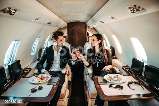 istock Successful couple making a toast with champagne glasses while having canapes aboard a private airplane 1092630192