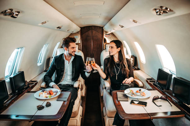 successful couple making a toast with champagne glasses while having canapes aboard a private airplane - enjoying wealthy life imagens e fotografias de stock