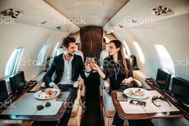 Photo of Successful couple making a toast with champagne glasses while having canapes aboard a private airplane
