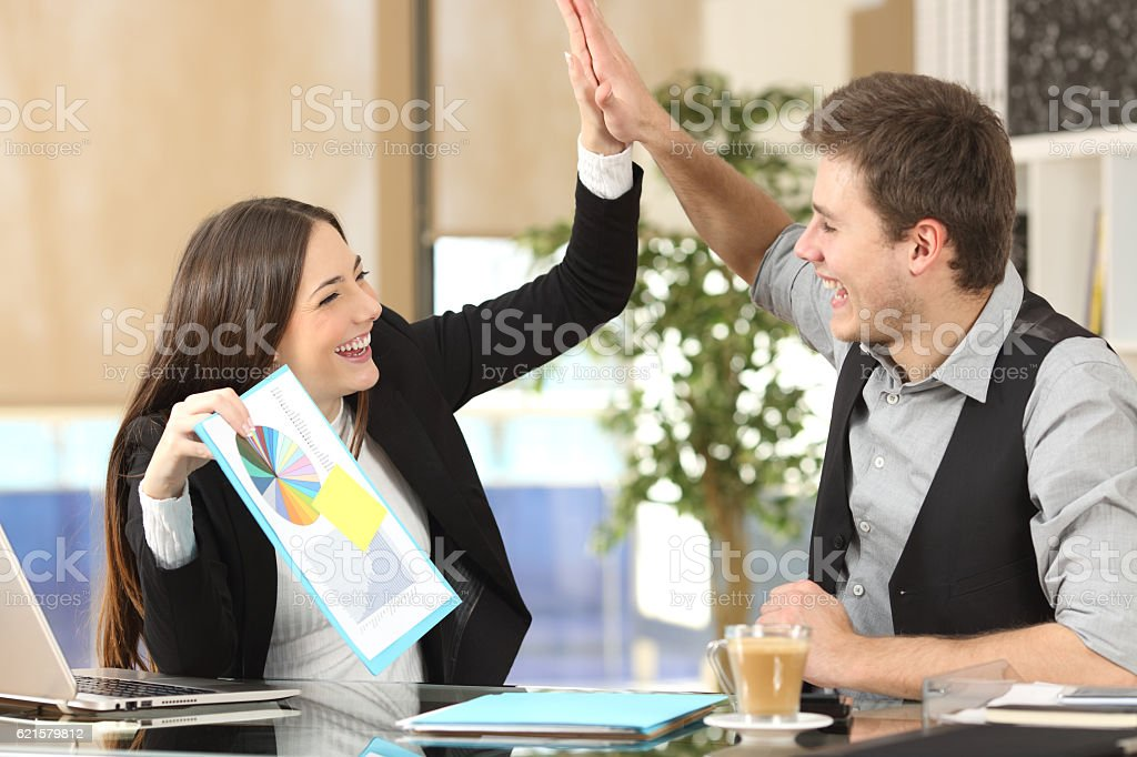Successful coworkers celebrating good results stock photo