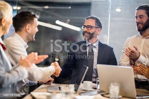 Happy businessmen shaping hands on a meeting in the office while their colleagues are applauding them. The view is through glass.