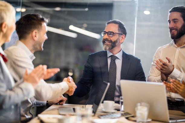 Successful deal in the office! Happy businessmen shaping hands on a meeting in the office while their colleagues are applauding them. The view is through glass. staff meeting stock pictures, royalty-free photos & images