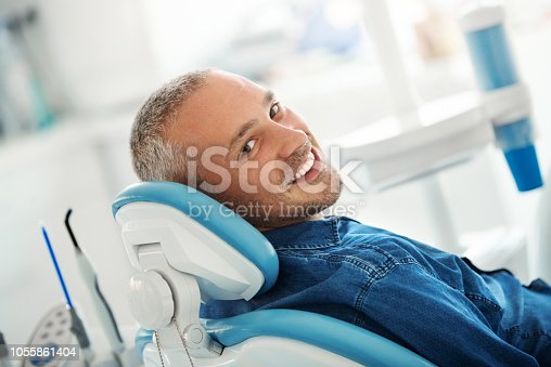 Closeup over the shoulder view of a cheerful early 40's male patient happily smiling to the camera after his dental procedure.