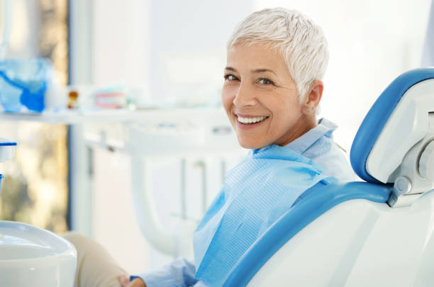 Successful dentist appointment. Closeup over the shoulder view of a cheerful mid 50's female patient happily smiling to the camera aftersuccessful dental procedure. dental health stock pictures, royalty-free photos & images
