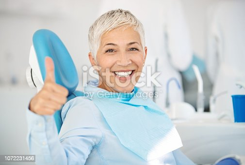 Closeup front view of a cheerful mid 50's female patient happily smiling to the camera and showing thumbs up after successful dental procedure.