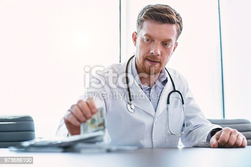 182362845 istock photo Successful doctor taking bribes in his office 973686100