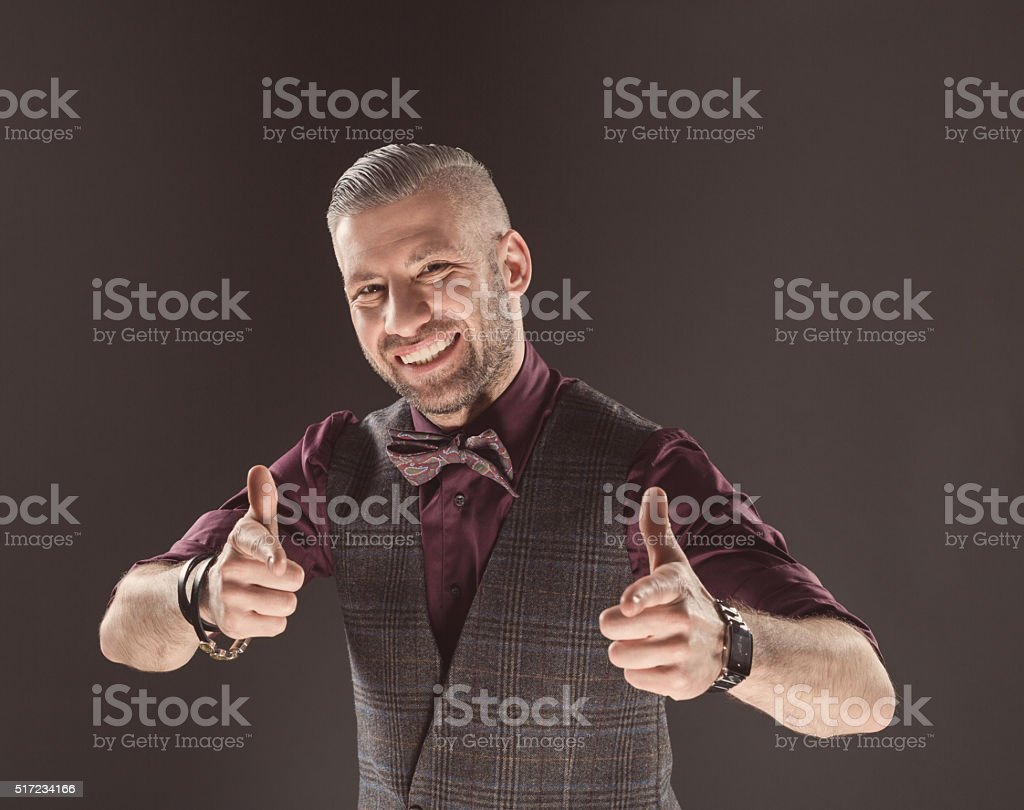 Successful elegant man wearing bow tie and tweed vest Happy elegant bearded man wearing tweed vest, shirt and bow tie, smiling at camera with thumbs up. Dark tone, black background. Adult Stock Photo