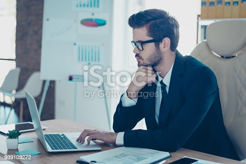 istock Successful entrepreneur  in black  formal wear with tie  sitting at his modern office and using laptop for his work 939103272