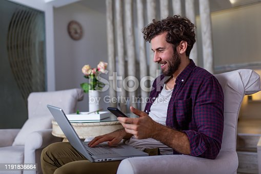 1127582480istockphoto Successful entrepreneur smiling in satisfaction as he checks information on his laptop computer while working in a home office. Young man relaxing on the sofa with a laptop and mobile phone in hands 1191836664