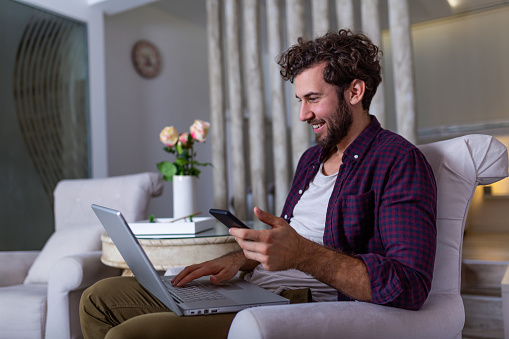 1127582480 istock photo Successful entrepreneur smiling in satisfaction as he checks information on his laptop computer while working in a home office. Young man relaxing on the sofa with a laptop and mobile phone in hands 1191836664