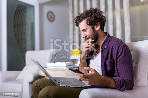 1127582480istockphoto Successful entrepreneur smiling in satisfaction as he checks information on his laptop computer while working in a home office. Young man relaxing on the sofa with a laptop and mobile phone in hands 1195542622