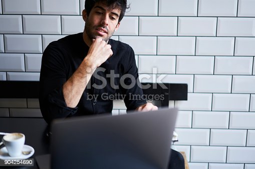 904263506 istock photo Successful entrepreneur thinking on business plan for his clients sitting in coffee shop with free wifi.Handsome owner watching interesting movie on modern computer with 4G internet connection 904254690