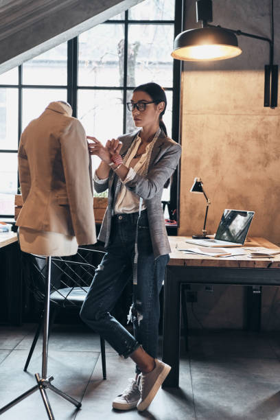 Successful fashion designer. Full length of serious young woman in eyewear using sewing needles for sewing a jacket on mannequin while standing in her workshop fashion designer stock pictures, royalty-free photos & images