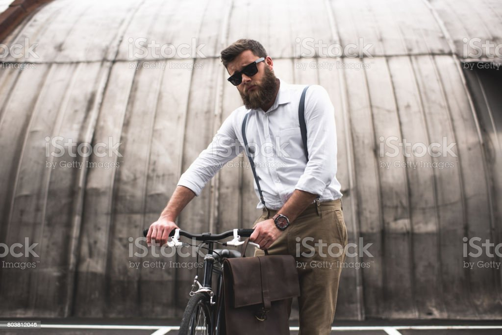 successful fashionable bearded man in sunglasses standing with bicycle stock photo