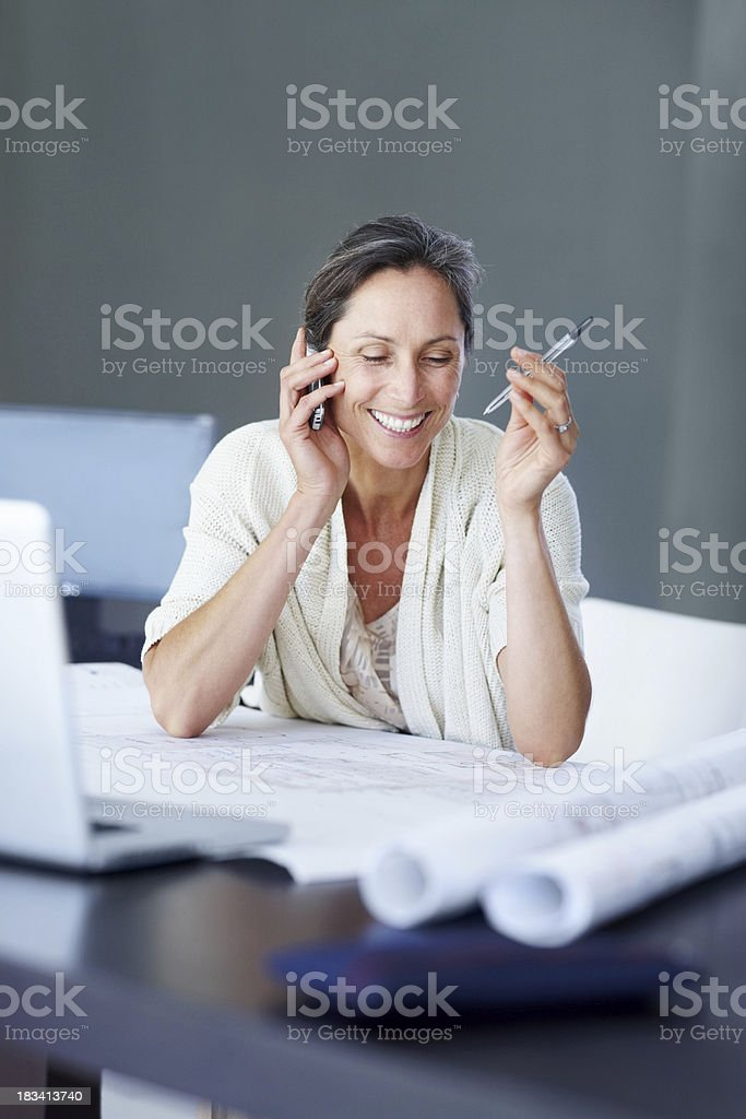 Successful female architect at her desk talking on cellphone royalty-free stock photo
