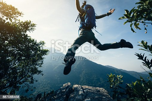 istock successful female backpacker jumping on cliff's edge 887088458