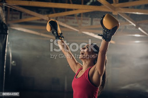 istock Successful female boxer celebrating her victory in a health club. 669944592