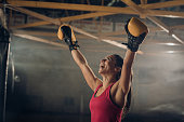 Joyful athletic woman celebrating her victory in a boxing match with her arms raised.