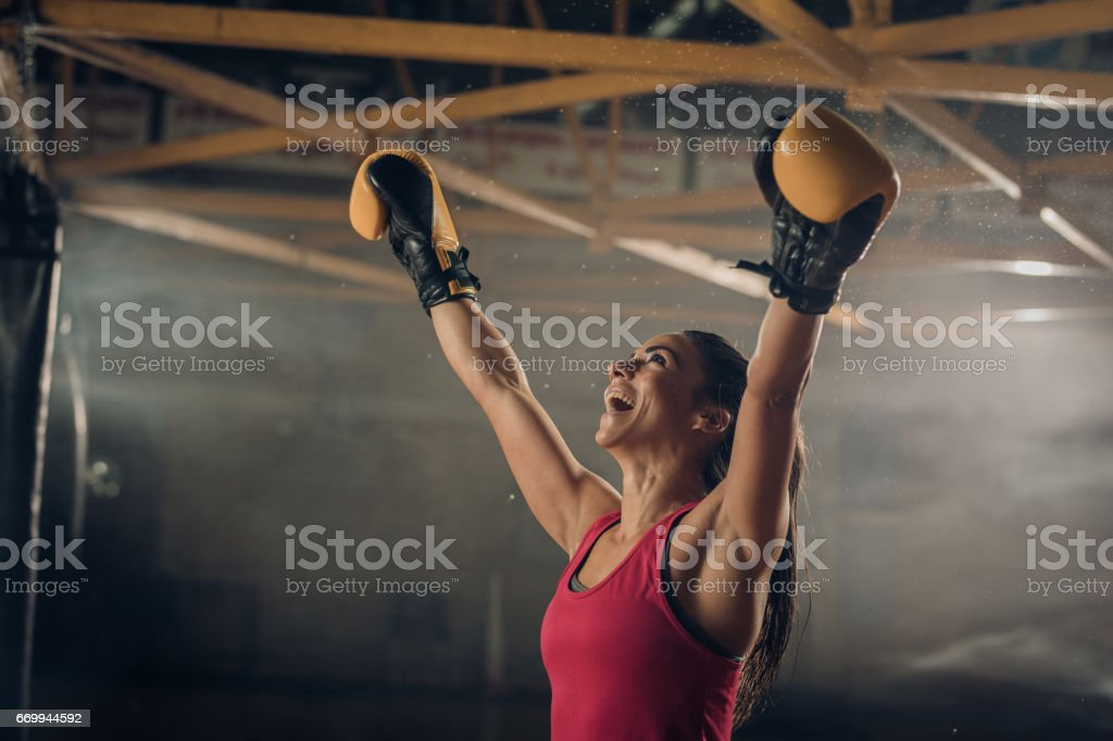 Successful female boxer celebrating her victory in a health club. stock photo