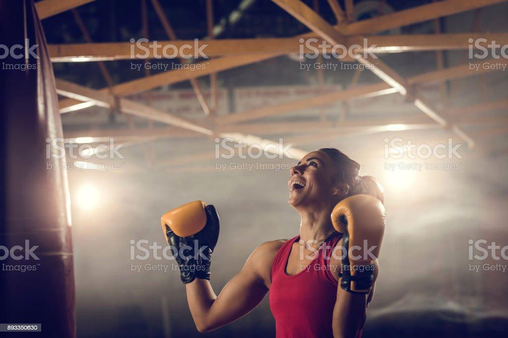 Boxer fêmea bem sucedido comemorando a vitória em um clube de saúde. - foto de acervo