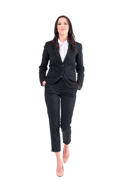 Successful female business manager or lawyer walking with hands in pockets. Successful female business manager or lawyer walking with hands in pockets. Full body isolated on white background. approaching stock pictures, royalty-free photos & images