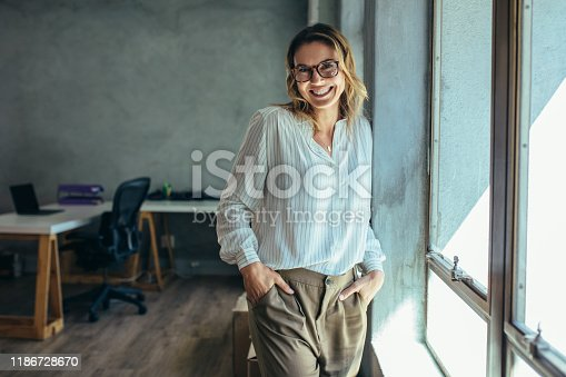 Successful female entrepreneur standing in office with hands in pocket. Businesswoman in casuals standing near window in office.