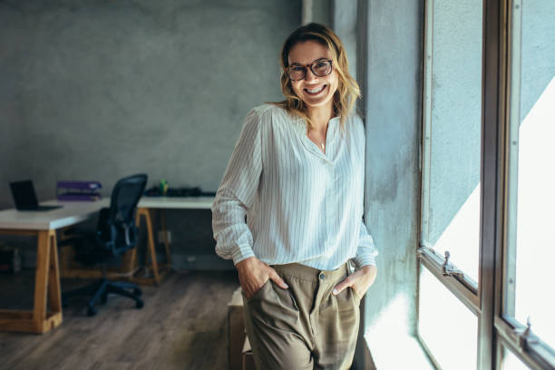Successful female entrepreneur Successful female entrepreneur standing in office with hands in pocket. Businesswoman in casuals standing near window in office. jacoblund stock pictures, royalty-free photos & images