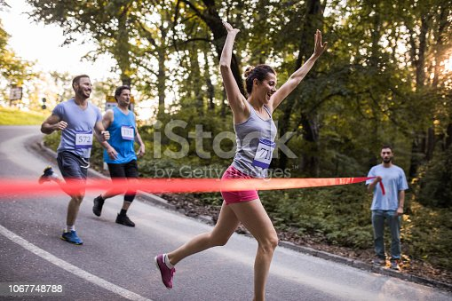 Happy woman winning a marathon race and crossing the finish line with her arm raised.