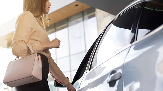 istock Successful female realtor getting into vehicle after working day in agency 962477526