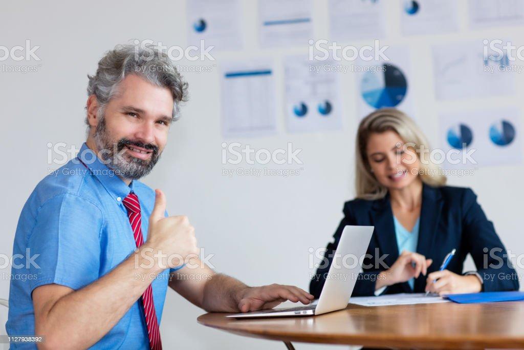 Exitoso hombre de negocios alemán con cabello gris y una computadora - foto de stock