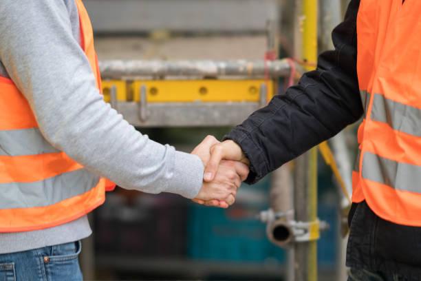erfolgreiche handshake deal auf baustelle - danke an lehrerin stock-fotos und bilder